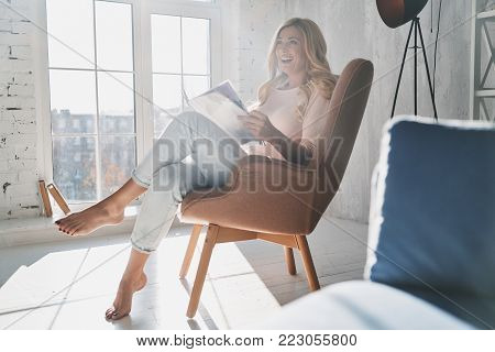 Enjoying reading. Beautiful young woman reading a magazine while sitting in the armchair at home