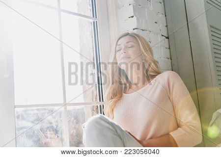 Feeling calm and happy. Attractive young woman keeping eyes closed and smiling while sitting on the window sill at home