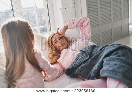 Time to wake up! Cute little girl waking up her beautiful mother while lying on the bed at home