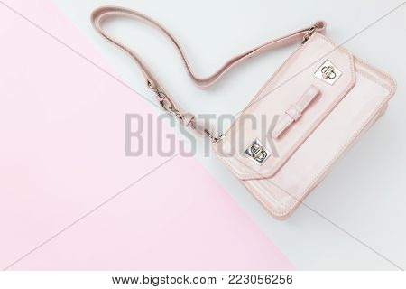 Table top view aerial image of fashion clothing background concept.beautiful pink hand bag of lady on pastel tone.Flat lay object on modern pink and white paper with copy space for creative design.