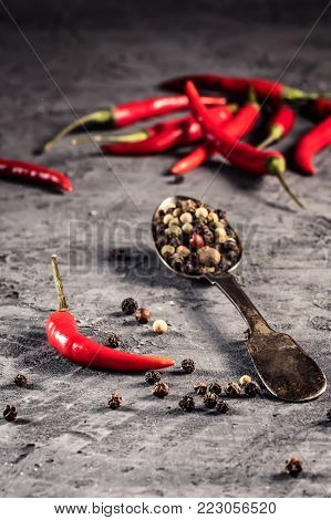 Red hot chilli pepper paprika in and peppers seed ball on stone table Ingredient for Mexican cooking Trendy toned image in minimal rustic style