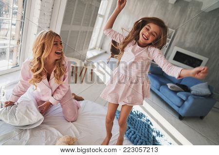 Going crazy together. Top view of cute little girl jumping on the bed while spending time with her mother at home
