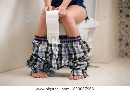 Girl in the morning sits on toilet seat