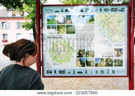 NEUF-BRISACH, FRANCE - JULY 11, 2010: tourist look on map of Neuf-Brisach town on square Place d'Armes General de Gaulle. Neuf-Brisach is a fortified town and commune in Haut-Rhin department in Alsace