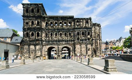 TRIER, GERMANY - JUNE 28, 2010: people near ancient roman monument Porta  (Black Gate) in Trier city. The Porta  was built in grey sandstone in 186-200 AD