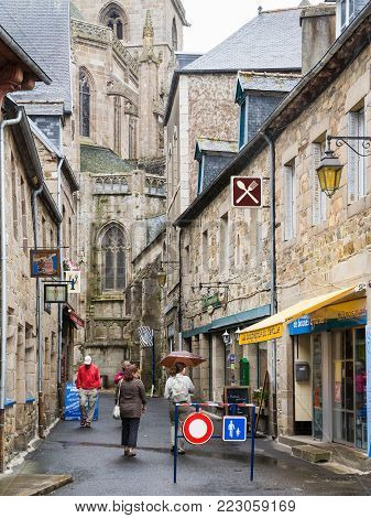 TREGUIER, FRANCE - JULY 2, 2010: tourists walk to Cathedral Saint-Tugdual along street Rue Ernest Renan in Treguier town. Treguier is port town in the Cotes-d'Armor department in Brittany.