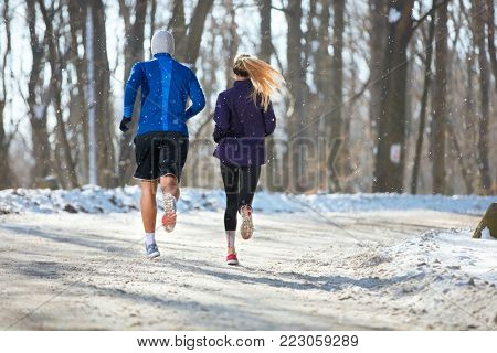 Young male and female jogging in nature at winter, back view