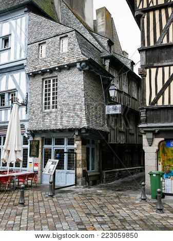 DINAN, FRANCE - JULY 5, 2010: medieval houses on square Place des Merciers in Dinan city in rain. Dinan is a walled town and commune in the Cotes-d'Armor department of Brittany