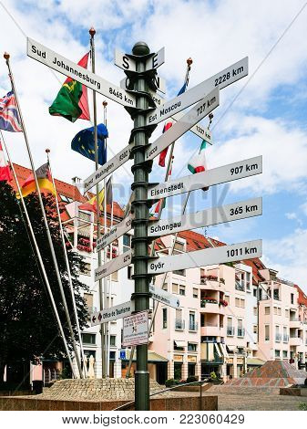 COLMAR, FRANCE - JULY 11, 2010: geographic marker with travel distance to cities and european flags on square Place de la Mairie in Colmar city. Colmar is the third-largest commune of Alsace region