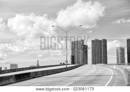 Miami Highway Or Public Road Roadway For Transport Vehicles And Urban Skyscrapers On Cloudy Blue Sky