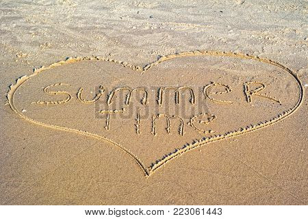 Words Summer time written in the sand on the beach..