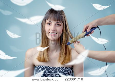 Pretty brunette woman at salon with plume around and ethereal concept