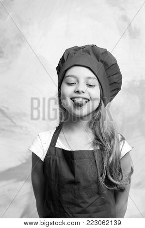 Small Girl Chef With Happy Face In Hat And Apron
