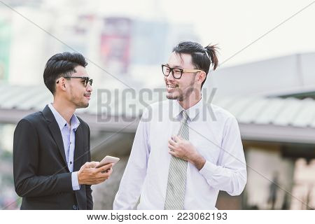 Having a break to talk around. Two cheerful business men talking and gesturing while standing outdoors