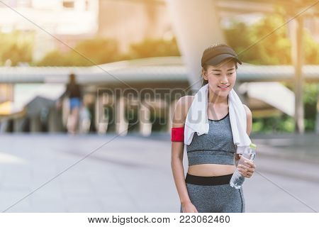 Portrait Beautiful girl with towel and bottle of water  female jogger drinking fresh water after training. Young athletic woman exercising in the city park outdoors.