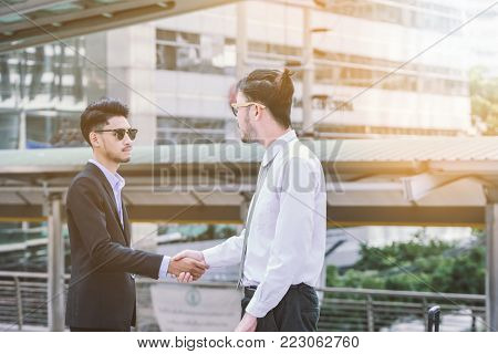 Business handshake concept. shaking hand of two businessman negotiation closing a deal city background