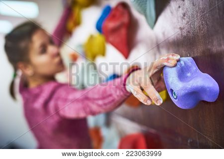 portrait of a sporty woman in boulder climbing hall. focus on a hand