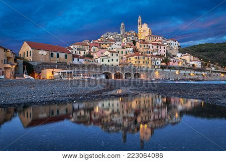 Old ligurian town Cervo reflecting in water at dusk, Province of Imperia, Liguria, Italy
