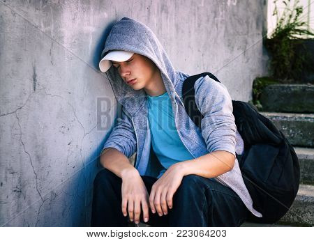 Toned Photo of Sad Teenager sit on the Street