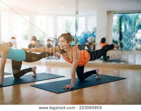 fitness, sport, training, yoga and people concept - Asian woman do exercise in gym.Group Of female Doing Yoga Indoors