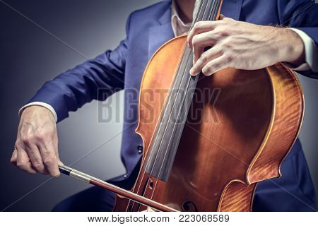 Cello player or cellist performing in an orchestra isolated