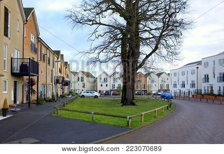 Bracknell,England - January 22, 2018: Wide angle view of modern homes and fully grown trees on a road through a housing estate in Bracknell, England