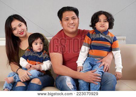 Happy Filipino family of four sitting on sofa