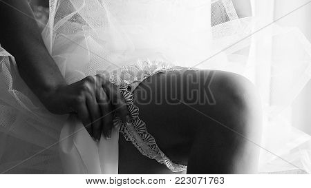 Close up hands of bride putting on beautiful white garter