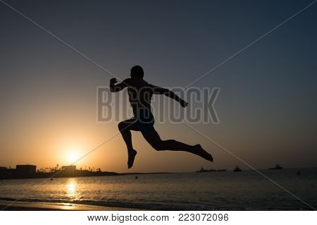 running man. silhouette of running man on sunset fiery sky background in sea, sport and recreation, future and success, people and nature, speed and healthy lifestyle