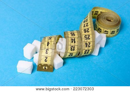 Fast carbohydrates give a lot of energy but make obesity problems overweight. Diets without sugar. A pile of white sugar cubes and a yellow measuring tape on a blue background.