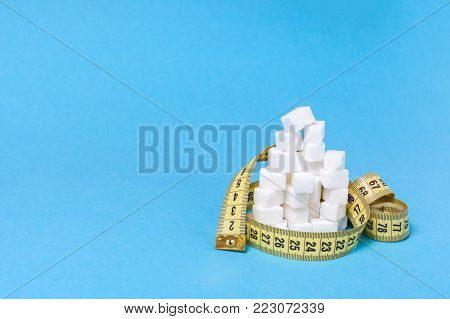 Fast carbohydrates give a lot of energy but make obesity problems overweight. Diets without sugar. A pile of white sugar cubes and a yellow measuring tape on a blue background. Copy space for text