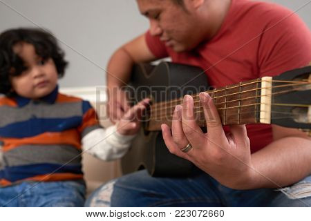 Filipino yuong mna playing guitar and signing for his son