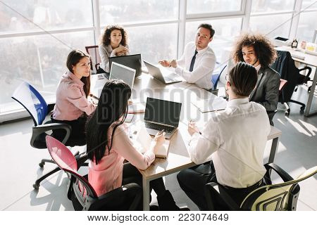 Business team sitting at round table. Discussing tasks of project. Office concept.