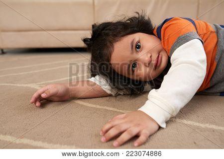 Adorable little Filipino kid resting on the floor