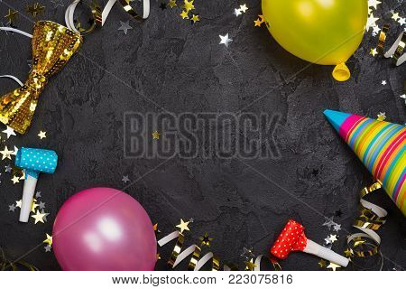Bright festive carnival background with hats, streamers, confetti and balloons. Copy space