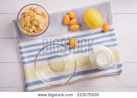 Bowl with corn flakes, jug of milk and empty bowl for prepared delicious breakfast.The concept of healthy breakfast, corn flakes with milk and fruit on wooden table, top view, flat lay.