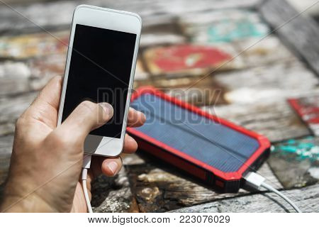 White smartphone in the hands of men on a colored background with Charging a smartphone phone from a solar panel.