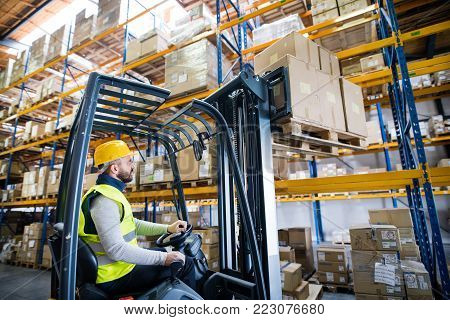 Man forklift driver working in a warehouse.