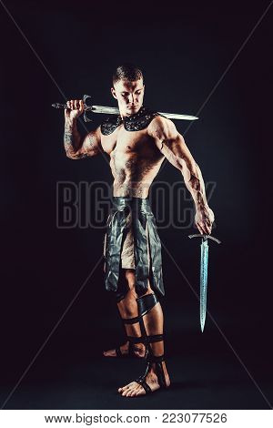 Portrait of handsome muscular gladiator with two swords. Studio shot. Black background.