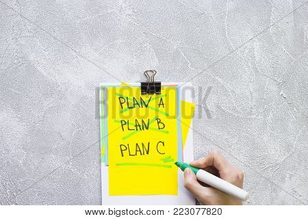 New Idea Creativity Business Concept with a copy space, colored paper and Plan A, Plan B, PlanC list clipped toghether, man crossing out items on a grey concrete background, flat lay, top view