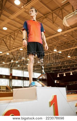 Dramatic full length portrait of young paralympic champion standing on winners pedestal in modern indoor stadium