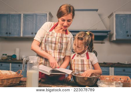 Cooking homemade cakes. Happy loving family are preparing bakery together. Mother and child daughter girl are cooking cookies and having fun in the kitchen. searching for recipes in a culinary book.
