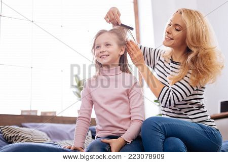 Comb. Pretty happy blond young mother smiling and combing her daughters hair while sitting behind her child