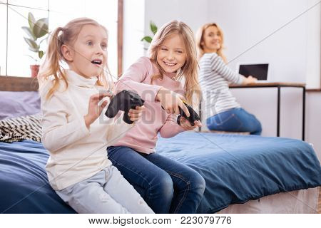 Game time. Lovely vigorous fair-haired little sisters smiling and holding remote controls while playing and hair mother working on the laptop