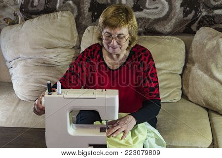 A woman is engaged in needlework at her leisure. Sitting on the couch in front of the sewing machine. Beginning of work.