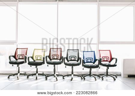 Modern office interior with colorful chairs chairs on big window background.