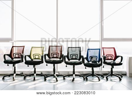 Colorful office chairs standing in a row at big window. Office concept.