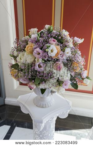 Big white flowerbed on pedestal with colorful flowers mostly roses with pastel shades in luxury royal restaurant with red decorative walls