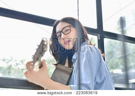 Music Concepts. Asian girls playing guitar. Asian women relaxing with music. Asian women have a happy lifestyle. Beautiful Asian girl playing guitar at home.
