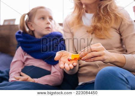 Pain killers. Unhappy sick little girl looking at her mother and wearing a scarf and lying in bed while her mom giving her the pills